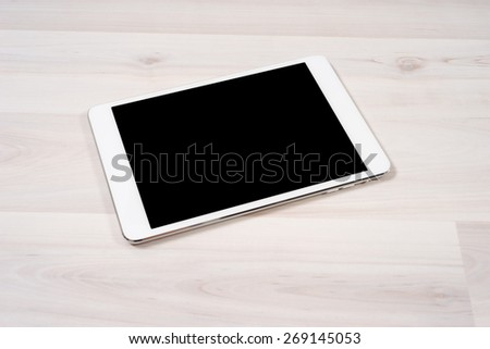 White digital tablet on wooden table - stock photo