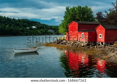 White dinghy in front of red buildings in the harbor at Conception Bay, Newfoundland - stock photo