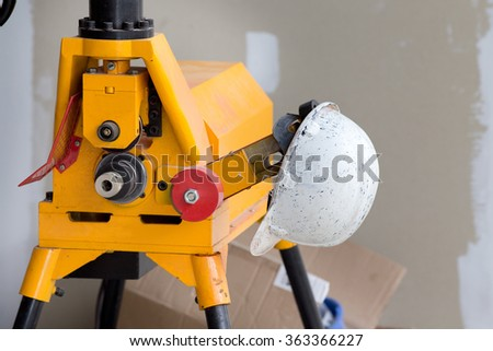 White dirty helmet from painter hanging on construction machine at building site - stock photo