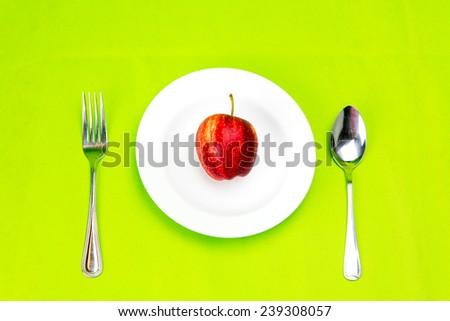 White dish and silver spoon and fork with red apple on green background - stock photo