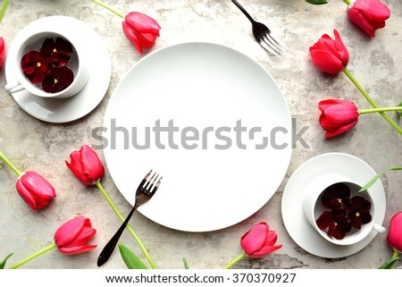 White dish were with red tulips on the silver background.spring flower arrangement. - stock photo