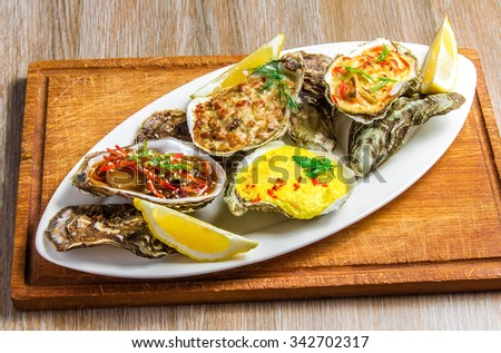 White dish with baked oyster shell with cheese, salad oysters, served greens and lemon on a wooden stand on the table.  - stock photo