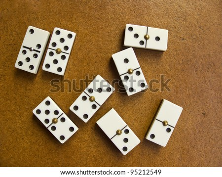 White domino pieces in rusty brown background - stock photo
