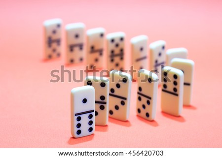 White dominoes standing in a row on red background - stock photo