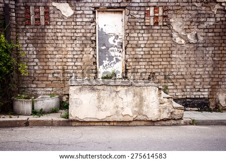 White door and steps  by the old street wall - stock photo