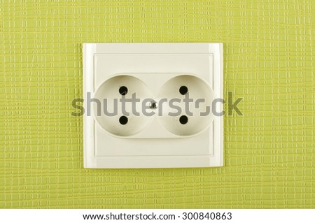 White double non-earthed AC electricity outlet on the green wall - stock photo