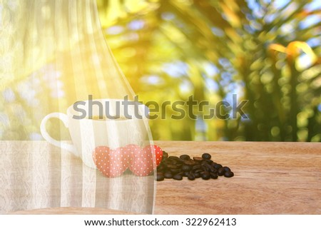 white drapery on cup of coffee and coffee seed with two red heart ,blur image of palm tree background - stock photo