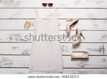White dress and sunglasses. White lace dress on shelf. Girl's new light evening garment. Casual evening outfit idea. - stock photo