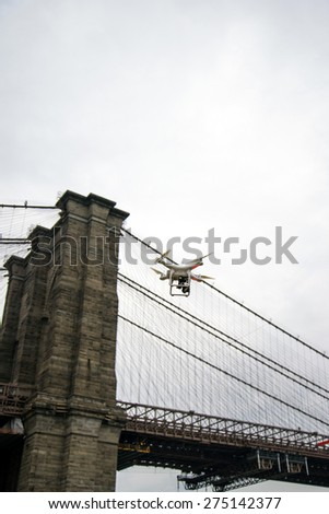 White drone flying by New York City's Brooklyn Bridge on a cloudy day - stock photo
