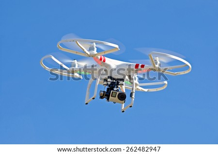 white drone hovering in a bright blue sky - stock photo
