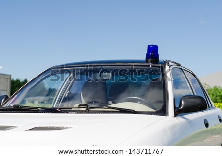 White duty car with blue flasher on top - stock photo