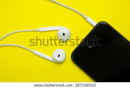 white earphones and mobile on yellow background. - stock photo