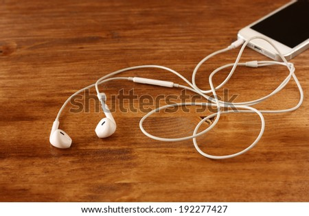 white earphones attached to smartphone. selective focus on earphones. - stock photo