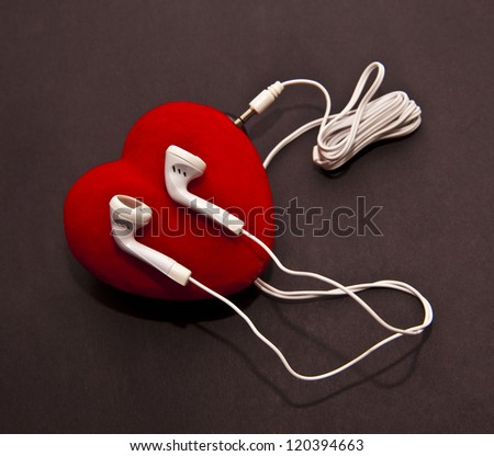 White Earphones  on a red heart on black  background - stock photo
