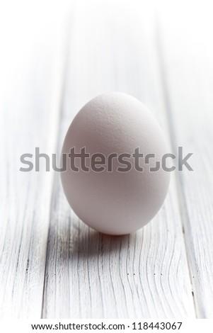 white egg on white wooden table - stock photo