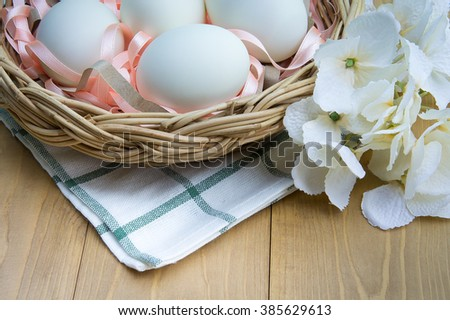 White eggs in the basket on the light wood table decorate with green and white fabric and white flowers.Eggs on wooden background. - stock photo