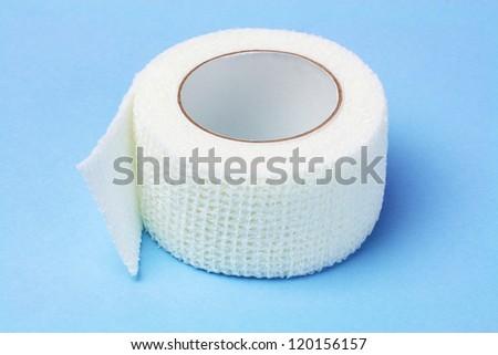 White Elastic Medical Bandage on Blue Background - stock photo