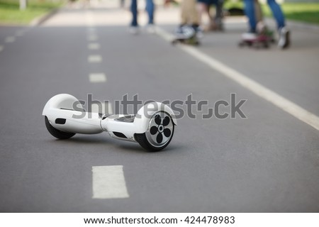 White Electric mini hover board scooter on road in park. Eco city transportation on battery power, produce no air pollution to atmosphere, care about planet - stock photo