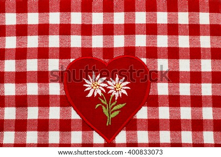 White embroidered Edelweiss flower on heart appliques in the center of the checkered red white tablecloth - stock photo