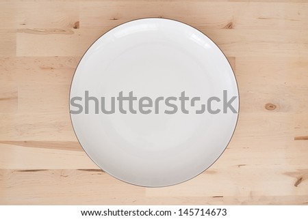 White empty plate on wooden background - studio shot - stock photo