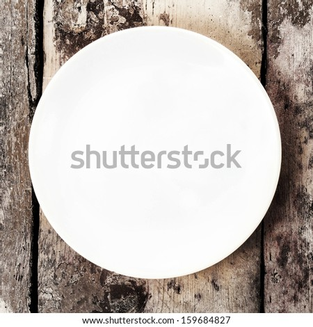 White empty plate with copy space for text on old wooden vintage background, top view closeup. - stock photo