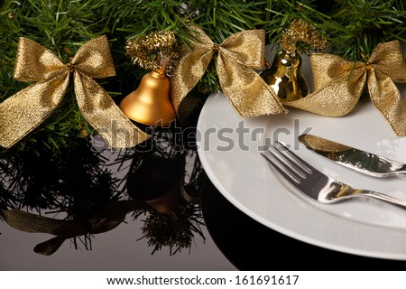 white empty plate with cutlery and Christmas ornaments on a table - stock photo