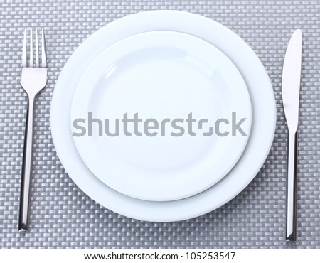White empty plates with fork and knife on a grey tablecloth - stock photo