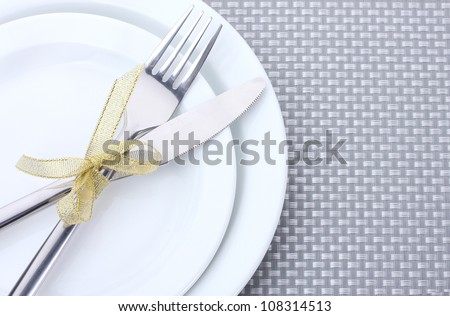 White empty plates with fork and knife tied with a ribbon on a grey tablecloth - stock photo