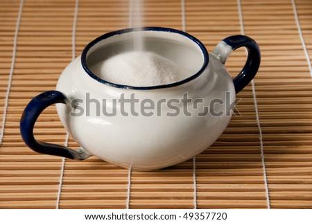 white enamel sugar bowl on a straw mat being filled - stock photo
