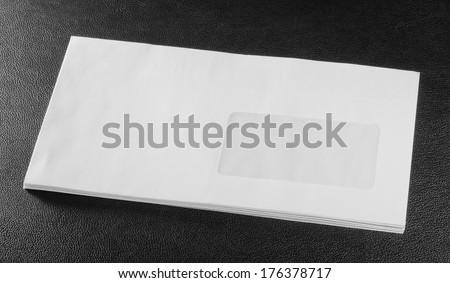 white envelope on black leather background - stock photo