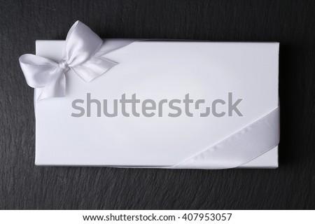 White envelope with ribbon on black background - stock photo