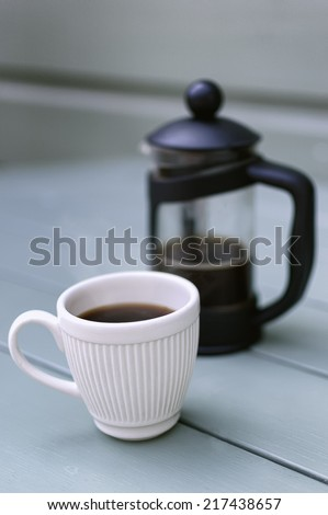 White Espresso Cup containing freshly brewed Coffee and a French Press/Cafetiere in an outdoor setting.  - stock photo