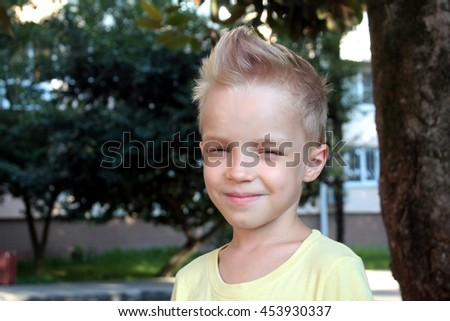 White european young boy smiling or squinted and looking directly at the camera - stock photo