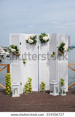 White fancy door as a wedding arch decorated with flowers and apples - stock photo