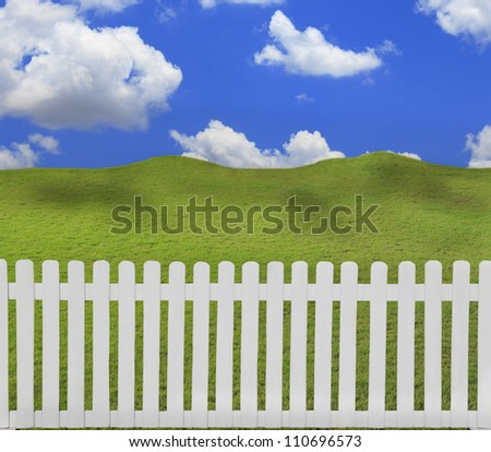 white fence and green field with cloud shadow - stock photo