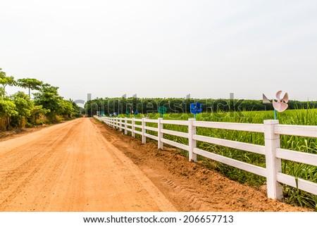 White fence in farm field - stock photo