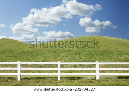 white fence in farm field with blue sky - stock photo