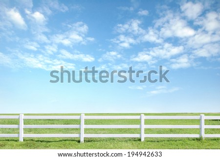 white fence on green grass with blue sky - stock photo