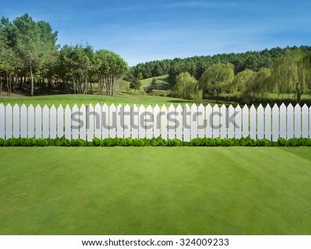 White fences on green grass - stock photo