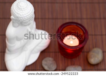 White figure in meditation pose with pebbles and candle in red glass from above - stock photo