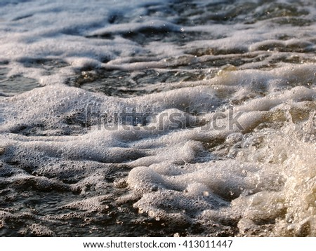 white fine bubbles flowing on water surface running from a pipeline direct onto a natural pond - stock photo