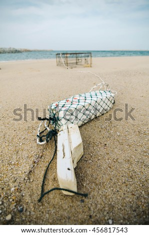 white fish buoy on sandy beach over crab pot background.focus on white buoy.shallow depth of field - stock photo