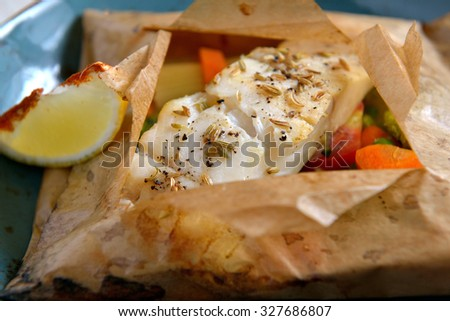 White fish fillet baked in paper, parchment with vegetables - stock photo
