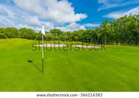 White flag and sand bunkers at the beautiful golf course. - stock photo