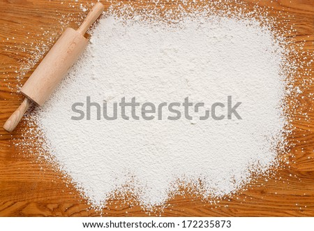 White flour on a wooden table creating a text area for insertion of your custom message or recipe - stock photo