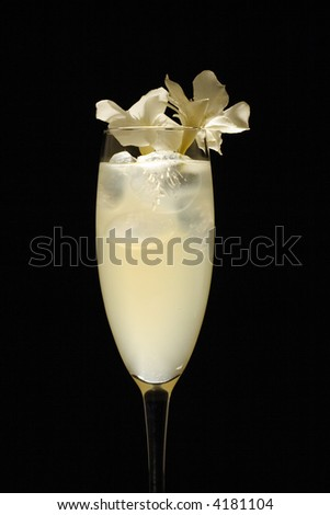 White flower decorated drink in studio light and black background - stock photo
