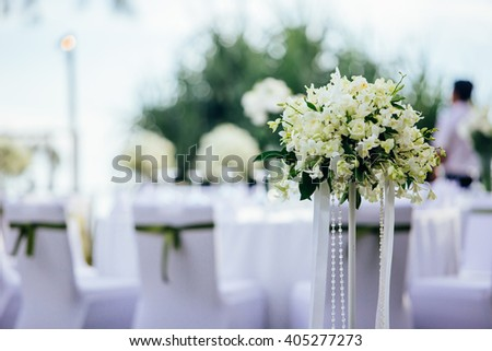 White flowers decorations during outdoor wedding ceremony on the beach - stock photo