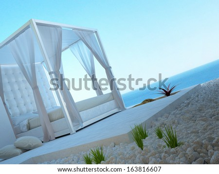 White four-poster bed standing outdoors with seascape view - stock photo