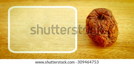 white frame and stinking red apple on wooden background - stock photo