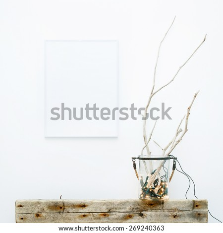 White frame with place for text. Mock up.  Hipster scandinavian style room interior. Jar with garland and weathered brunches. Creative lightning. - stock photo